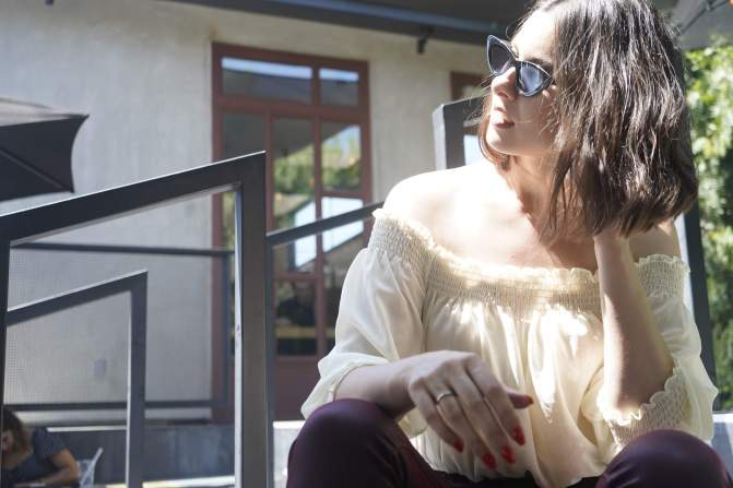 Writer Elyse Hauser sitting in the sun and thinking, wearing sunglasses.